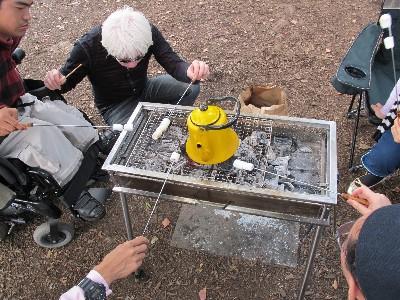 コンロの中央にポットがあります。まわりでマニュマロを焼いています。