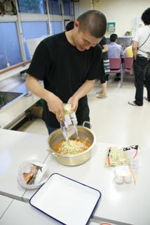 スタッフ高作がお鍋に野菜を投入